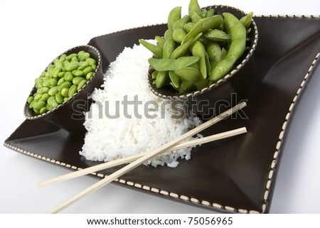 Edamame soy beans with white rice in a brown ceramic dish. - stock photo