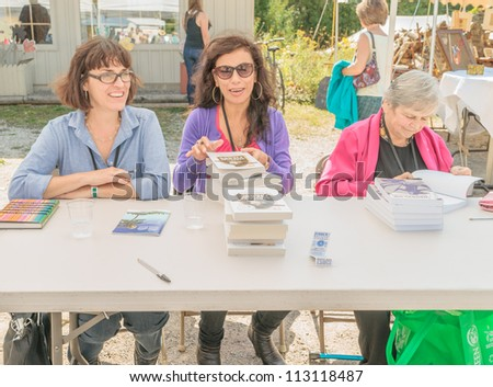 EDEN MILLS, ON - SEPTEMBER 16:  Canadian writers Nora Young, Carmen Aguirre and Michele Landsberg sign their books at the annual Writers Festival in Eden Mills, Ontario on September 16, 2012. - stock photo