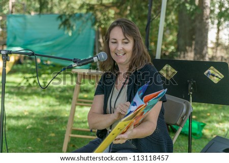 EDEN MILLS, ON - SEPTEMBER 16:  Children's author, Lizann Flatt, reads from her recent book  to an audience of children at the annual Writers Festival in Eden Mills, Ontario on September 16, 2012. - stock photo