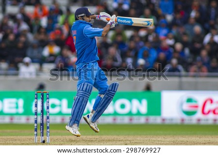 EDGBASTON, ENGLAND - June 23 2013: India's Mahendra Singh Dhoni hits the ball and is dismissed off the bowling of Ravi Bopara during the ICC Champions Trophy final  match between England and India - stock photo