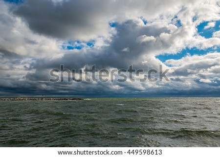 Edge of the concrete pier in the stormy Baltic sea - stock photo