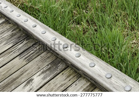 Edge of weathered wooden boardwalk across grassy wetland in a public park in spring, northern Illinois - stock photo
