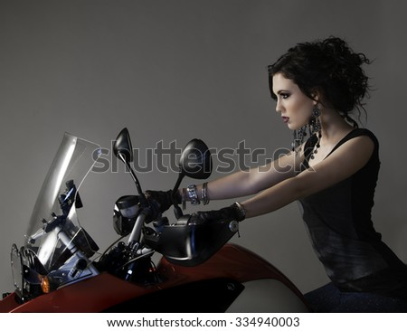 Edgy brunette woman seated on red motorcycle. - stock photo