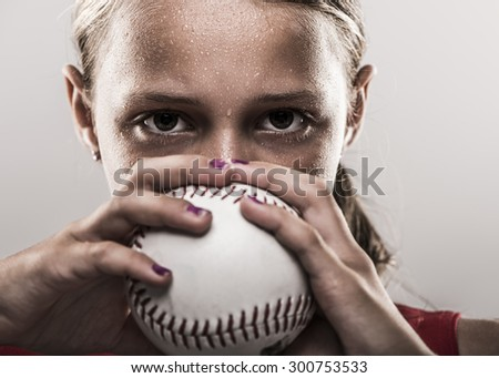 Edgy softball girl with sweat looking from behind a softball - stock photo