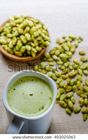 Edible seeds of hyacinth bean snack and green tea latte on wood background - stock photo