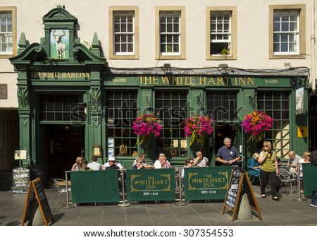 EDINBURGH - AUGUST 17, 2015:  People having food and drink in a classical pub in Edinburgh, Scotland.  In many places, especially in villages, a pub can be the focal point of the community.  - stock photo