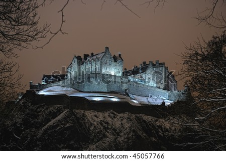 Edinburgh Castle, Scotland, UK, illuminated at night in the winter snow - stock photo