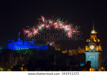Edinburgh Cityscape night scene with fireworks over The Castle and Balmoral Clock Tower - stock photo