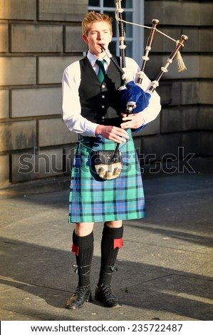 EDINBURGH - DEC 31: Unidentified Scottish Bagpiper playing music with bagpipe at Edinburgh on December 31.2013 in Scotland. - stock photo
