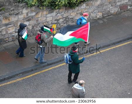 EDINBURGH - JANUARY 10: A pro-Palestinian protester displays the Palestinian flag during an anti-Israel march through central Edinburgh January 10th, 2009 in Edinburgh, Scotland. - stock photo