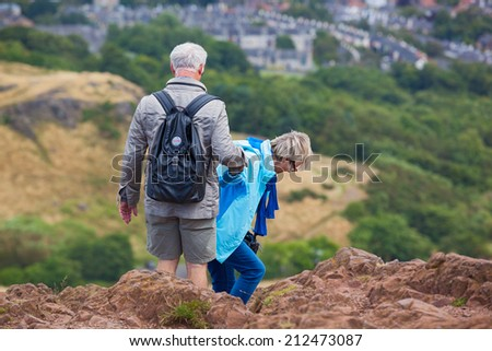 EDINBURGH, SCOTLAND: AUGUST 4, 2014: Elderly couple climbing down the hill in Holyrood Park. Arthur's seat is popular destination for hiking and enjoying nature.  - stock photo