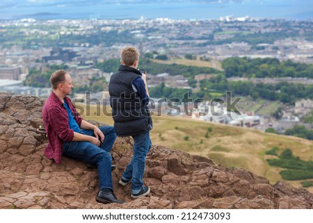 EDINBURGH, SCOTLAND: AUGUST 4, 2014: Father and son enjoying the view from the Arthur's seat in Holyrood Park. Arthur's seat is popular destination for hiking and enjoying nature.  - stock photo