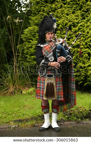 EDINBURGH, SCOTLAND - JULY 28 2015 : Unidentified Scottish Bagpiper playing music with bagpipe in Scotland.  Bagpipes are a class of musical instrument, aerophones, and have been played for centuries. - stock photo