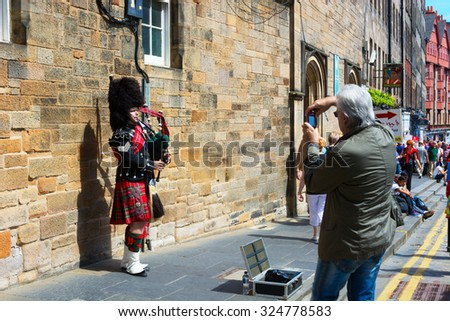 EDINBURGH, SCOTLAND - JUNE 12, 2015: Scottish Bagpiper playing his bagpipe in the Old Town of Edinburgh in Scotland  - stock photo