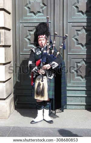 EDINBURGH, SCOTLAND, UK - CIRCA AUGUST 2015: Scottish bagpiper dressed in traditional green, blue and black tartan dress - stock photo