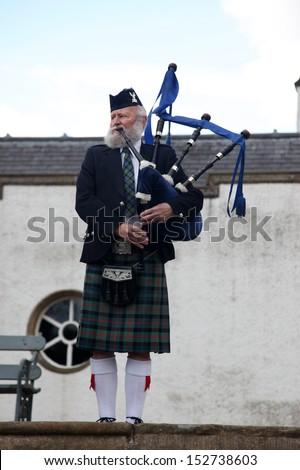 EDINBURGH, SCOTLAND, UNITED KINGDOM - JUNE 16 : Unidentified Scottish Bagpiper playing music with bagpipe at Edinburgh on June 16, 2011. Edinburgh is the most popular tourist destination in Scotland - stock photo