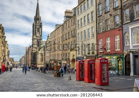 Edinburgh, Uk - March 28, 2015: Traditional Telephone booths on the Royal Mile. The Royal Mile runs downhill between the Castle and Holyrood Palace and is the busiest tourist street in the Old Town. - stock photo