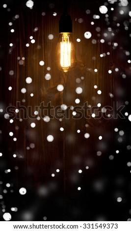 Edison light bulb. lantern with snowfall - stock photo