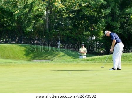 EDISON,NJ-AUGUST 26: Golfer Ernie Els watches his putt during the second round of the Barclays Tournament held at the Plainfield Country Club on August 26, 2011 in Edison, N.J. - stock photo