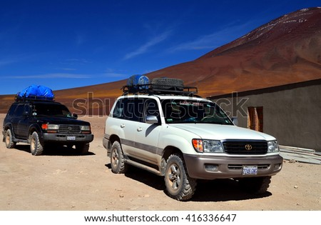 EDUARDO AVAROA NATIONAL RESERVE OF ANDEAN FAUNA, BOLIVIA - AUGUST 30, 2014: Two tourist cars near the bolivian border checkpoint, Bolivia - stock photo