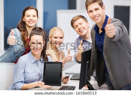 education, advertisement, techology and internet concept - group of smiling students with computer monitor and blank black tablet pc screen - stock photo
