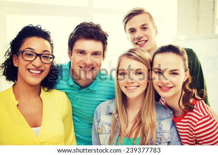 education and happiness concept - group of young smiling people at home or school - stock photo