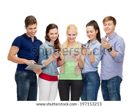 education and modern technology concept - smiling students using smartphones and tablet pc - stock photo