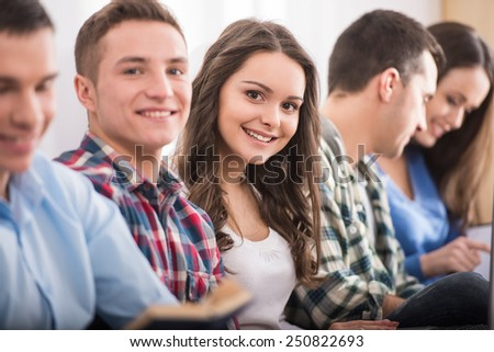 Education and people concept. Group of students are sitting on the floor, some of them looking at the camera. - stock photo