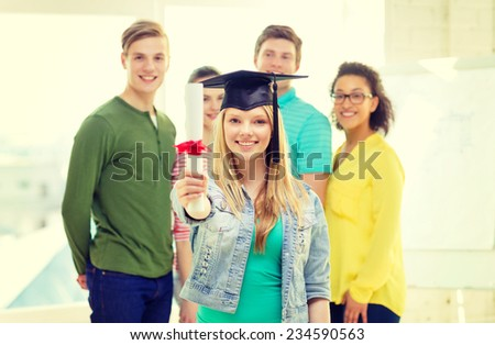 education and people concept - smiling female student with diploma and corner-cap and friends on the back - stock photo