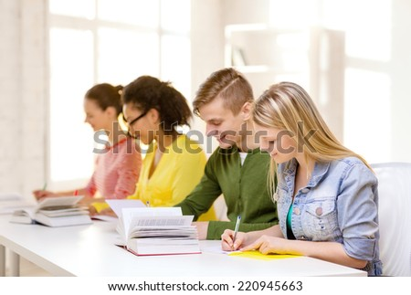 education and school concept - five smiling students with textbooks and books at school - stock photo