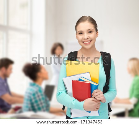 education and school concept - happy and smiling teenage girl with backpack and books - stock photo