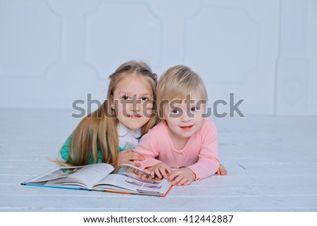 education and school concept - little sisters lying on a floor with a book studying and reading. happy kids boys brothers reading encyclopedia together at home  - stock photo