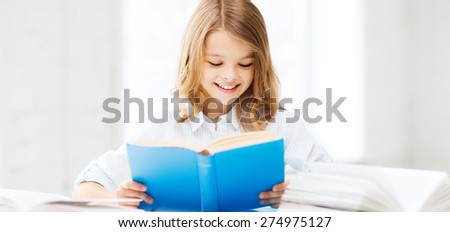 education and school concept - little student girl studying and reading book at school - stock photo