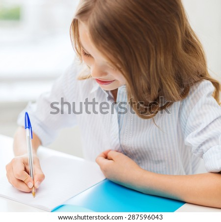 education and school concept - little student girl writing in notebook at school - stock photo