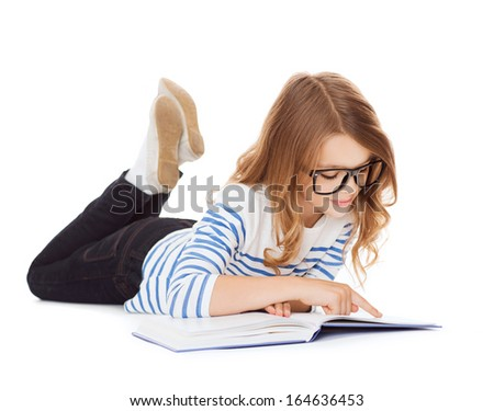 education and school concept - smiling little student girl with book and eyeglasses lying on the floor - stock photo