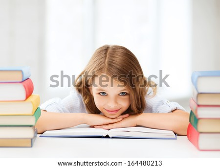 education and school concept - smiling little student girl with many books at school - stock photo