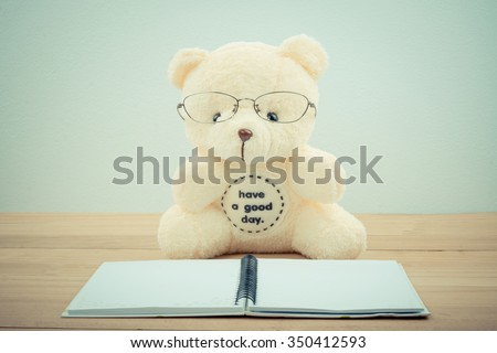 education and school concept - vintage image of teddy bear  happy to studying and reading book - stock photo
