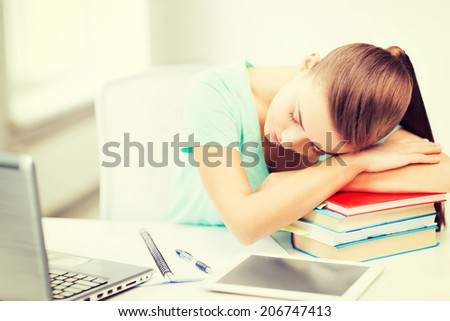 education and technology concept - tired student sleeping on stack of books - stock photo