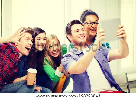 education and technology - group of students making picture with tablet pc at school - stock photo