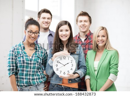 education and time concept - group of students at school with clock - stock photo