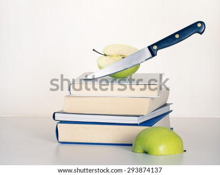 Education budget cuts. Knife slashes into teacher's apple. Concept. - stock photo