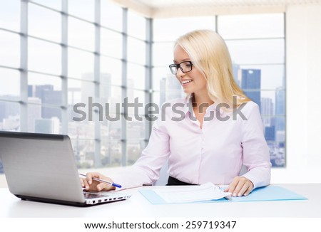 education, business and technology concept - smiling businesswoman with laptop computer and papers sitting over office room with city view window background - stock photo