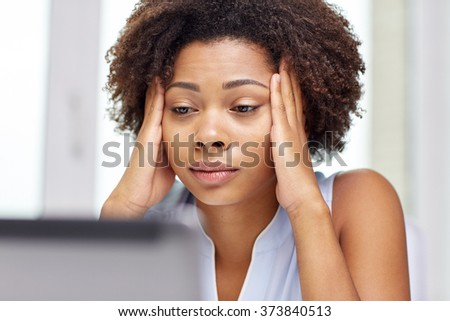 education, business, fail and technology concept - african american businesswoman or student with laptop computer and papers at office - stock photo