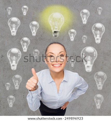 education, business, inspiration, gesture and people concept - smiling young woman in eyeglasses having idea and showing thumbs up over gray background with light bulbs - stock photo
