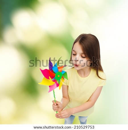 education, childhood and ecology concept - smiling child with colorful windmill toy - stock photo