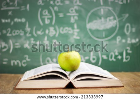 Education concept, book and apple in the background of the blackboard - stock photo