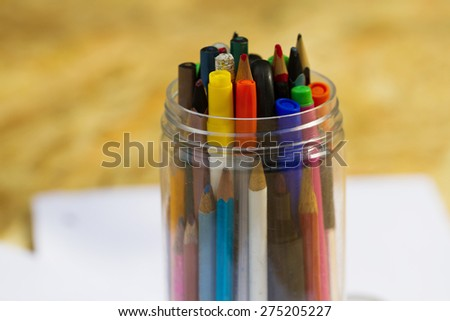 Education concept. Close-up view of school supplies in a glass jar - stock photo