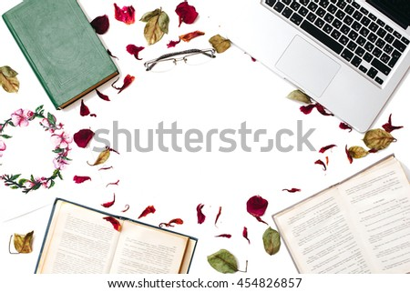 Education concept. Frame of books, textbooks, laptop, glasses, leaves and petals isolated on white background. Flat lay - stock photo