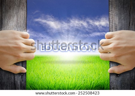 Education concept. Hand opening an old wooden door and found a texts floating over green field and bright blue Sky Sunrise. - stock photo
