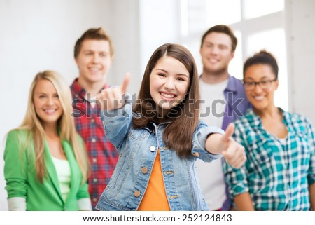 education concept - happy team of students showing thumbs up at school - stock photo